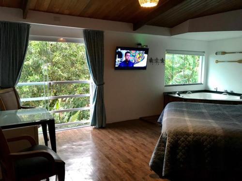 Uma TV ou centro de entretenimento em Suites na Casa da Praia