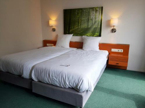 A bed or beds in a room at Fletcher Landhotel Bosrijk Roermond