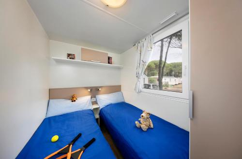 A bed or beds in a room at Albatross Mobile Homes on Camping Cisano & San Vito S. p. A.