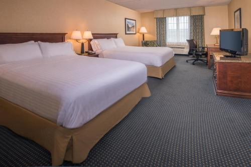 A bed or beds in a room at Holiday Inn Express State College at Williamsburg Square, an IHG Hotel