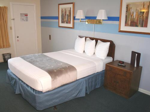 A bed or beds in a room at Lake Lighthouse Inn