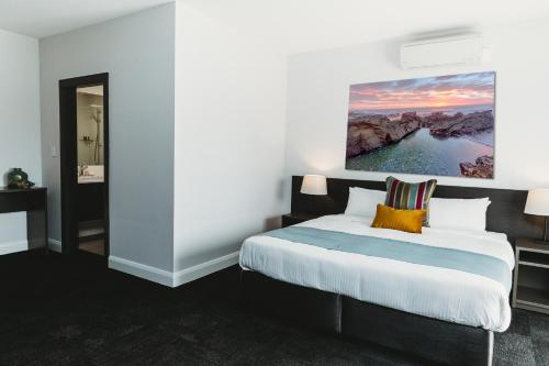 A bed or beds in a room at Coniston Hotel Wollongong