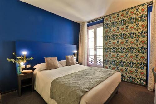 A bed or beds in a room at Hôtel Le G (ex Le Genève)