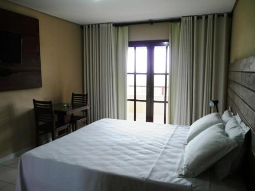A bed or beds in a room at Pousada Calugi