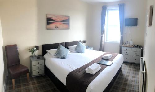 A bed or beds in a room at The Anglers Inn