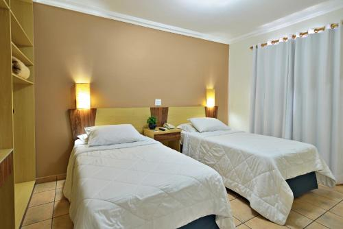 Кровать или кровати в номере Plaza Inn Flat Araxá