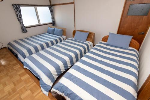 A bed or beds in a room at Guesthouse TAKADA