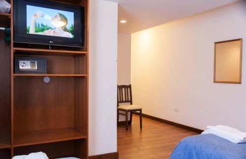Uma TV ou centro de entretenimento em Hotel Premier Bariloche