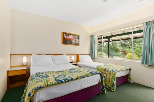 A bed or beds in a room at Solomon Inn Wollongong