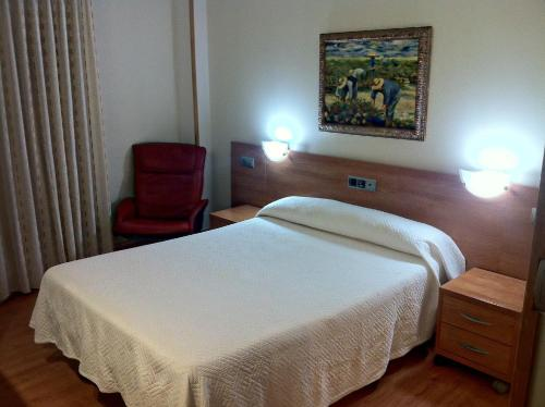 A bed or beds in a room at Hostal Del Carmen