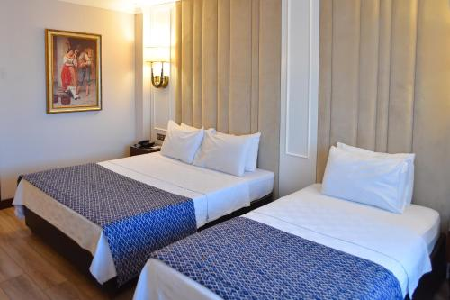 A bed or beds in a room at Golden Lake Hotel