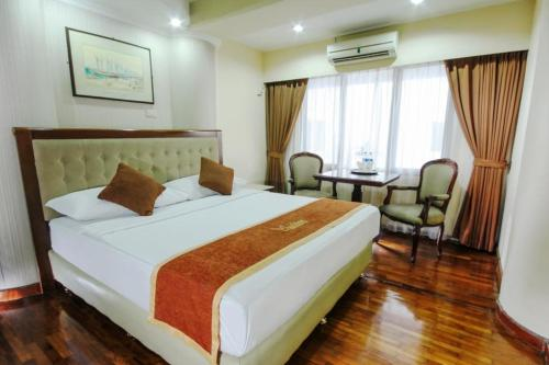 A bed or beds in a room at Grand Menteng Hotel
