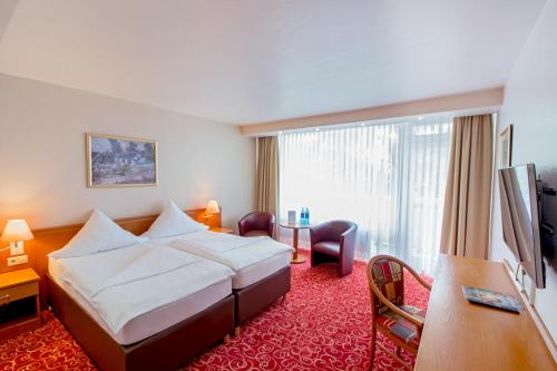 A bed or beds in a room at Caravelle Hotel im Park