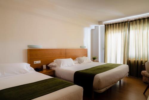 A bed or beds in a room at Hotel Crisol de las Rías