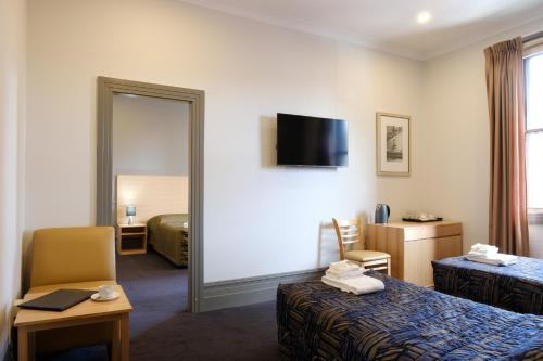A bed or beds in a room at Royal Exhibition Hotel