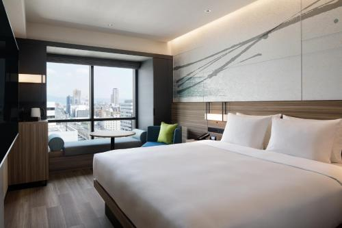 A bed or beds in a room at Courtyard by Marriott Osaka Honmachi