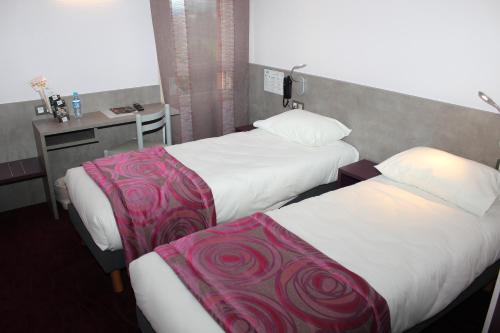 A bed or beds in a room at Brit Hotel Les Evens