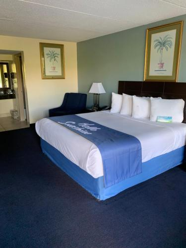 A bed or beds in a room at Days Inn by Wyndham Orlando Airport Florida Mall