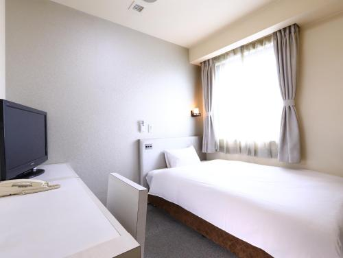 A bed or beds in a room at Hotel Wing International Himeji