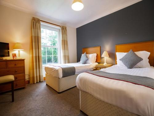 A bed or beds in a room at The Gables Hotel