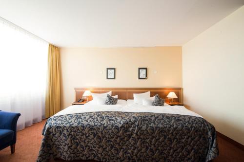 A bed or beds in a room at Carathotel Basel/Weil am Rhein