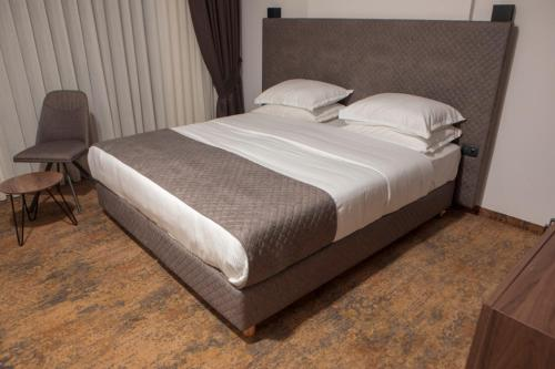A bed or beds in a room at Qama Hotel