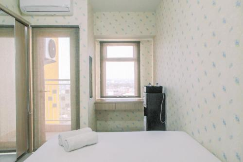 A bed or beds in a room at Modern Furnished Studio at Springlake Summarecon Bekasi Apartment By Travelio