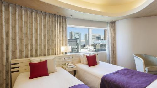 A bed or beds in a room at Hotel Elsereine Osaka