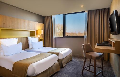 A bed or beds in a room at Domaine du Gouverneur, Hôtel, Restaurant & Golf