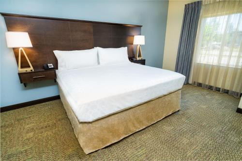 A bed or beds in a room at Staybridge Suites Corona South, an IHG Hotel