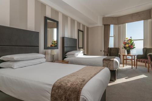 A bed or beds in a room at Queens Hotel & Spa