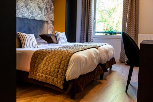 A bed or beds in a room at La Tour Hotel-Restaurant