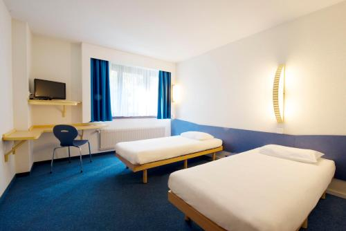 A bed or beds in a room at ibis budget Szczecin