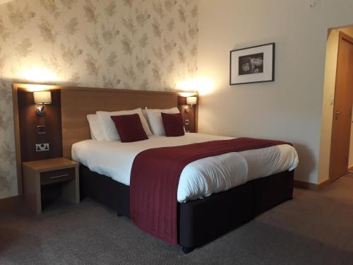 A bed or beds in a room at Weald of Kent Golf Course and Hotel