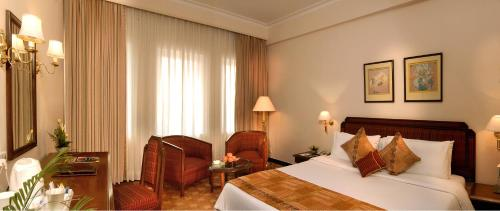 A bed or beds in a room at The Peerless Inn Kolkata