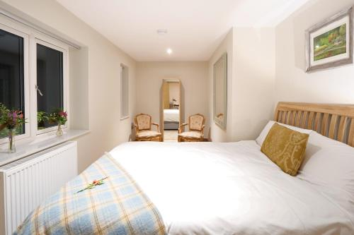 A bed or beds in a room at Pinetum Garden Cottages