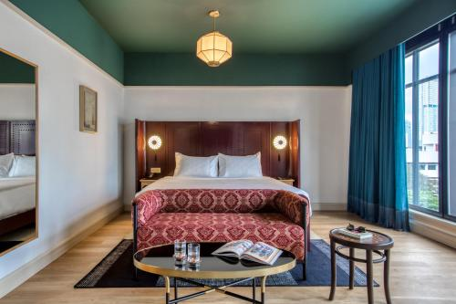 A bed or beds in a room at The Chow Kit - an Ormond Hotel