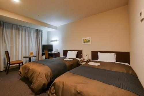 A bed or beds in a room at Hotel Continental Fuchu