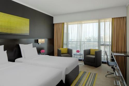 سرير أو أسرّة في غرفة في بولمان دبي كريك سيتي سنتر