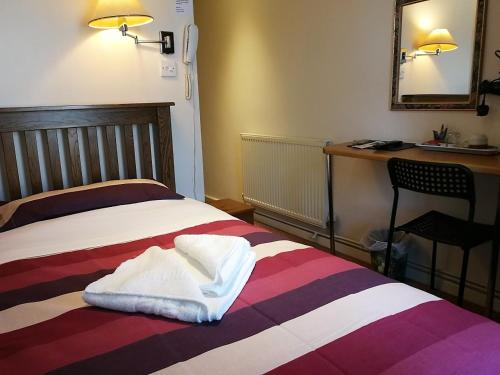 A bed or beds in a room at Ascot Grange Hotel - Voujon Resturant