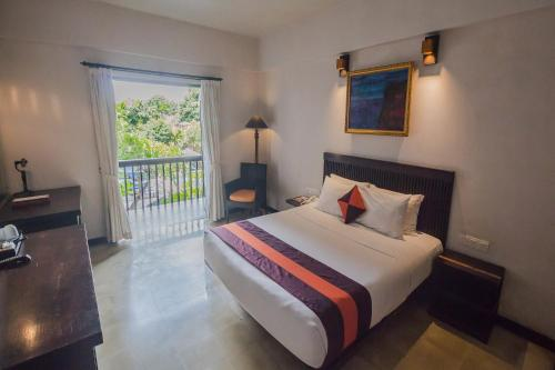 A bed or beds in a room at The Lokha Legian Resort & Spa