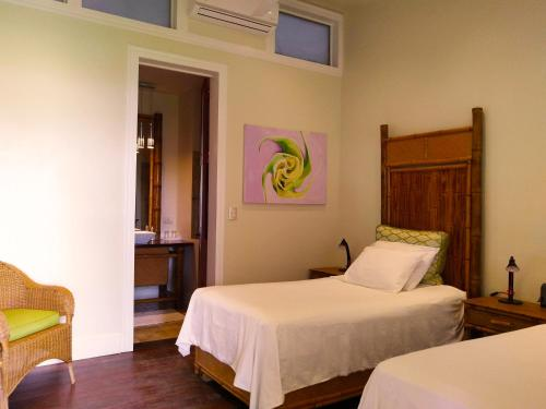 A bed or beds in a room at Iguana Lodge Beach Resort and Spa