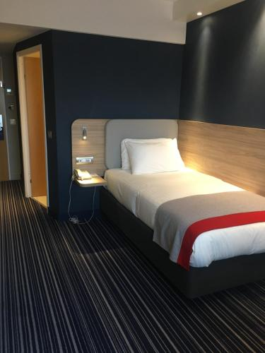 A bed or beds in a room at Holiday Inn Express Geneva Airport, an IHG Hotel