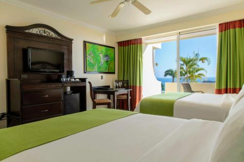 A bed or beds in a room at Parador Resort and Spa