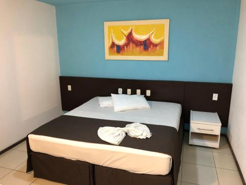 A bed or beds in a room at Saint Patrick Praia Hotel