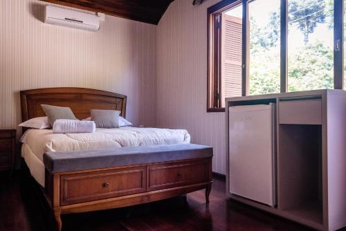 A bed or beds in a room at Hospedagem Vila Suíça