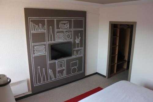 A television and/or entertainment centre at ibis Mons Centre Gare