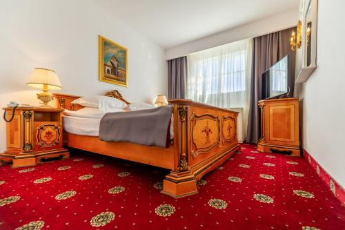 A bed or beds in a room at Hotel Imparatul Romanilor