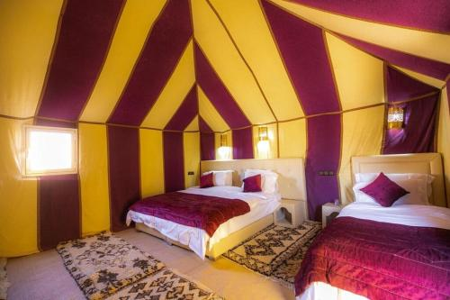 A bed or beds in a room at Dunes Luxury Camp