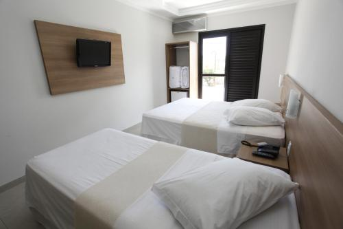 A bed or beds in a room at Hotel Recreio São Jorge